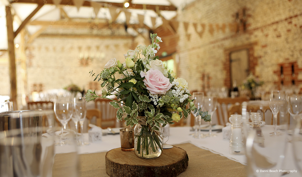 Rustic table centrepieces are used to decorate the tables in the South Barn at Upwaltham Barns