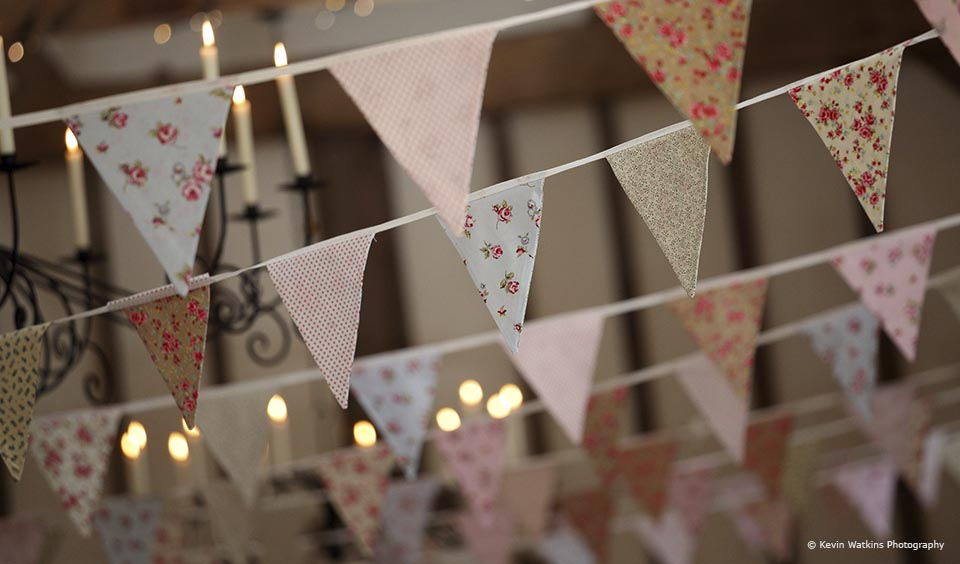 Traditional bunting hangs from the wedding barns at Upwaltham Barns for a country wedding