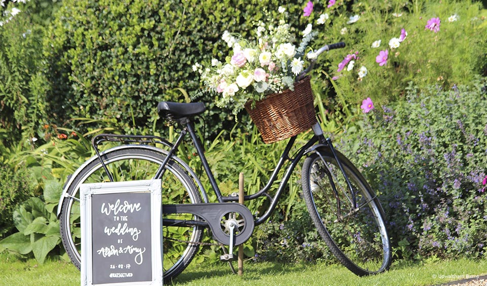 A vintage bike is used to welcome guests to a wedding at Upwaltham Barns