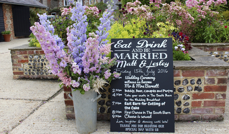 A sign provides guests with timings for the wedding day at Upwaltham Barns