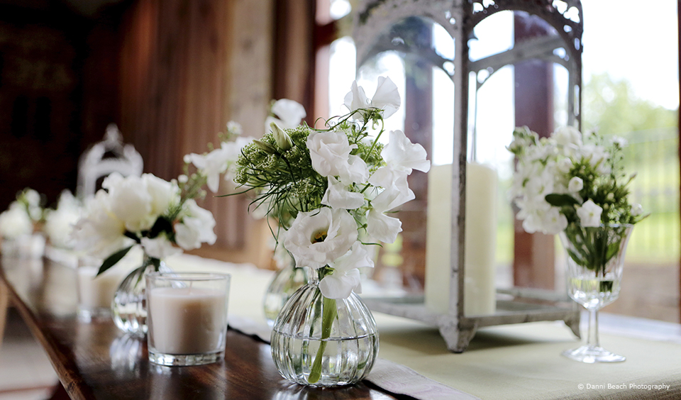White wedding flowers are placed in glass vases for an elegant wedding look at Upwaltham Barns