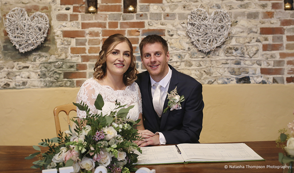 The bride and groom sign the wedding register after saying their vows in a winter wedding ceremony at Upwaltham Barns