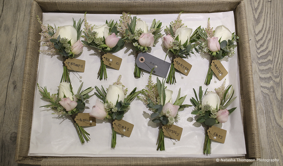 White and pink flowers make up the buttonholes for a winter wedding at Upwaltham Barns