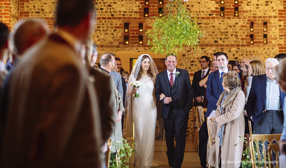 The bride and her father walk down the aisle in the South Barn at Upwaltham Barns