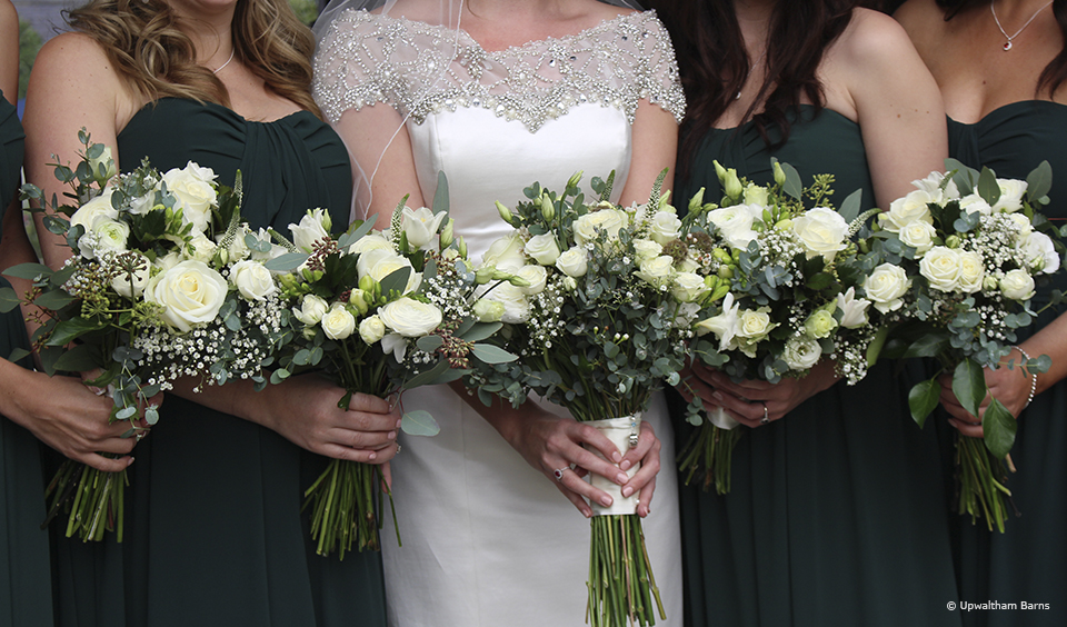Bridesmaids wear dark green dresses for a winter wedding at Upwaltham Barns