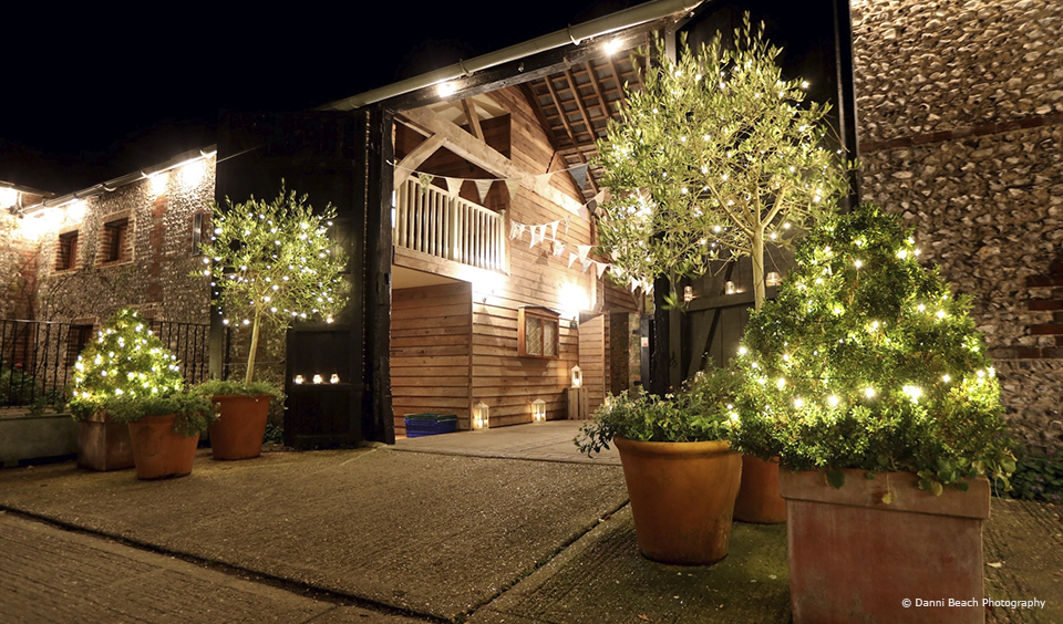 The Courtyard at Upwaltham Barns is decorated with fairy lights for a winter wedding