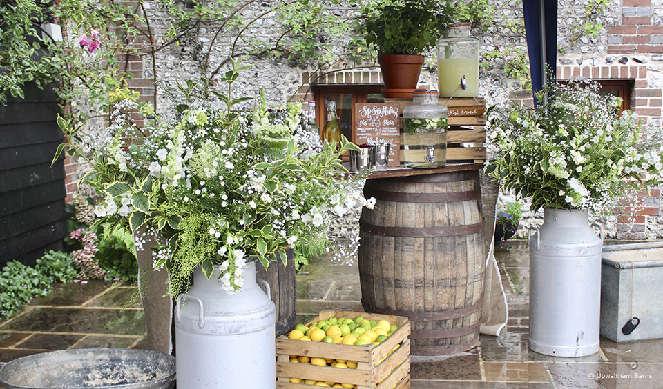 Barrels are used to create a drinks station for an autumn wedding at Upwaltham Barns