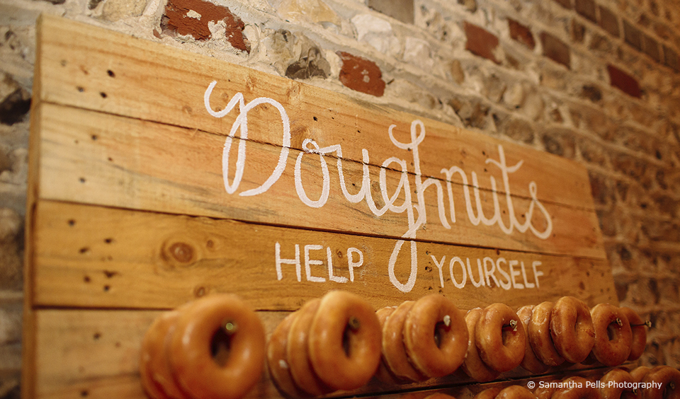 The couple created a doughnut wall as a focal point for their winter wedding at Upwaltham Barns