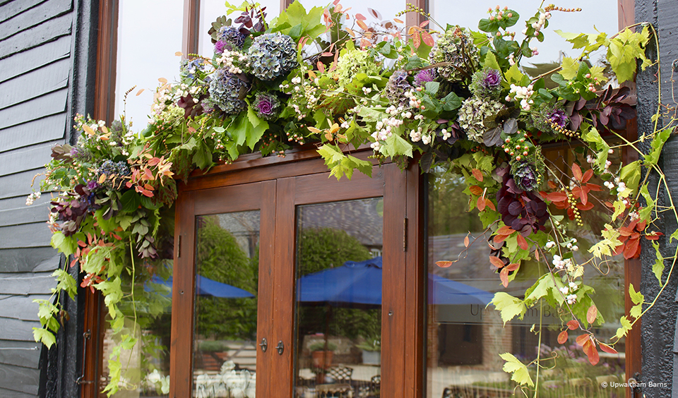 An autumnal flower garland hangs above the entrance to the East Barn at this West Sussex wedding venue