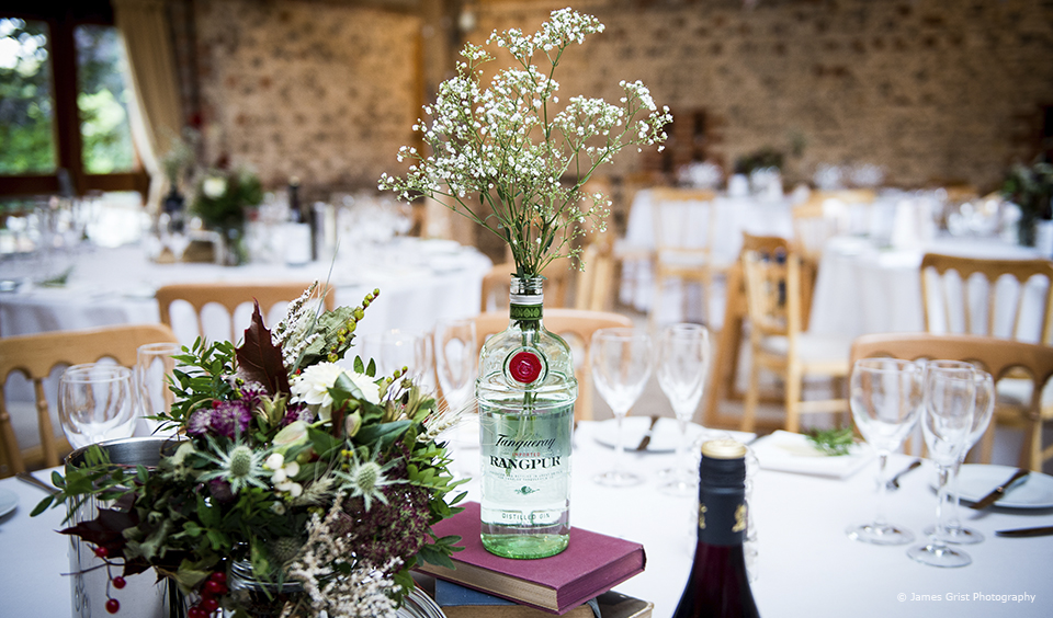 Rich coloured florals add elegance to a table centrepiece for a winter wedding at Upwaltham Barns