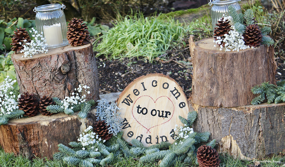 Logs are decorated with pine cones for a winter wedding at Upwaltham Barns