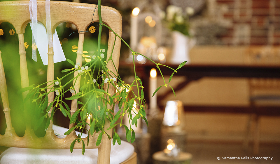 For the winter wedding ceremony in the East Barn at Upwaltham Barns mistletoe was hung on pew ends