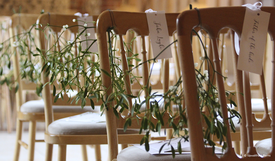 Hang mistletoe on pew ends at Upwaltham Barns for a festive touch to a winter wedding