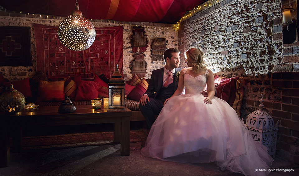 Newlyweds share a moment in the Moroccan Snug at Upwaltham Barns during their winter wedding