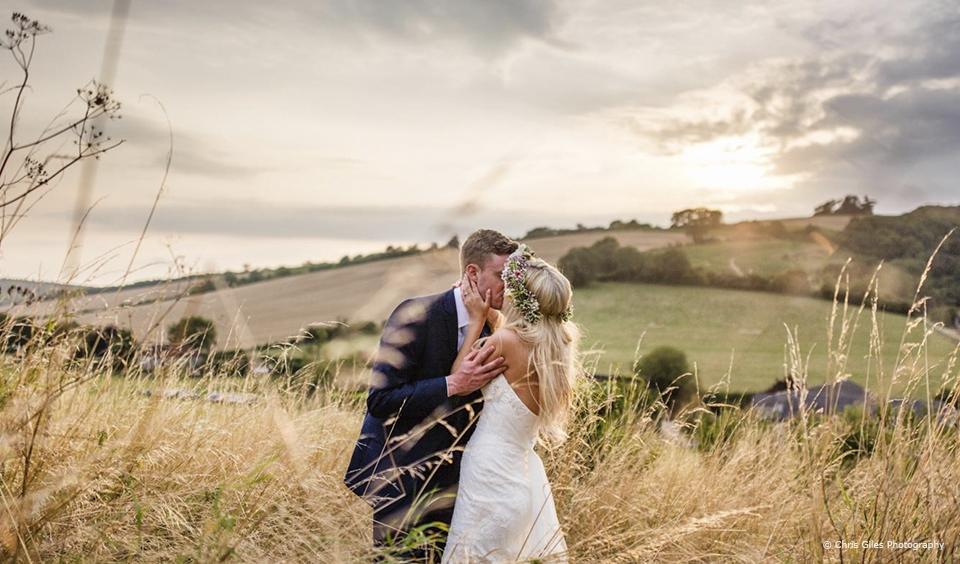 A couple use the autumnal light and countryside surrounding Upwaltham Barns for a beautiful wedding photo