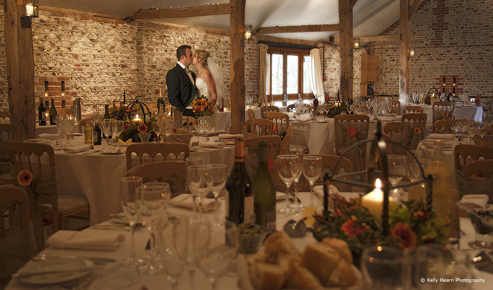 Newlyweds admire the cosy lanterns that dress the South Barn for their autumn wedding at Upwaltham Barns