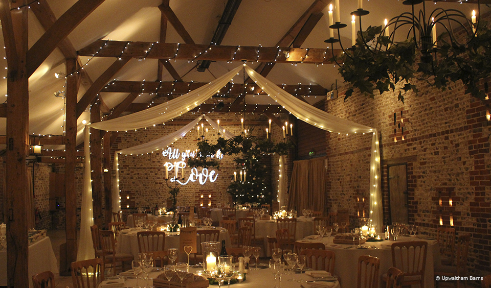 The South Barn is decorated with fairy lights for a winter wedding at Upwaltham Barns