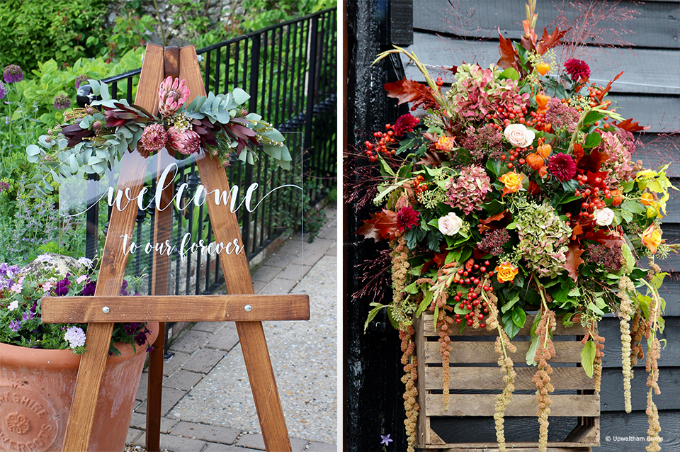 A welcome wedding sign at Upwaltham Barns is decorated with autumn wedding flowers