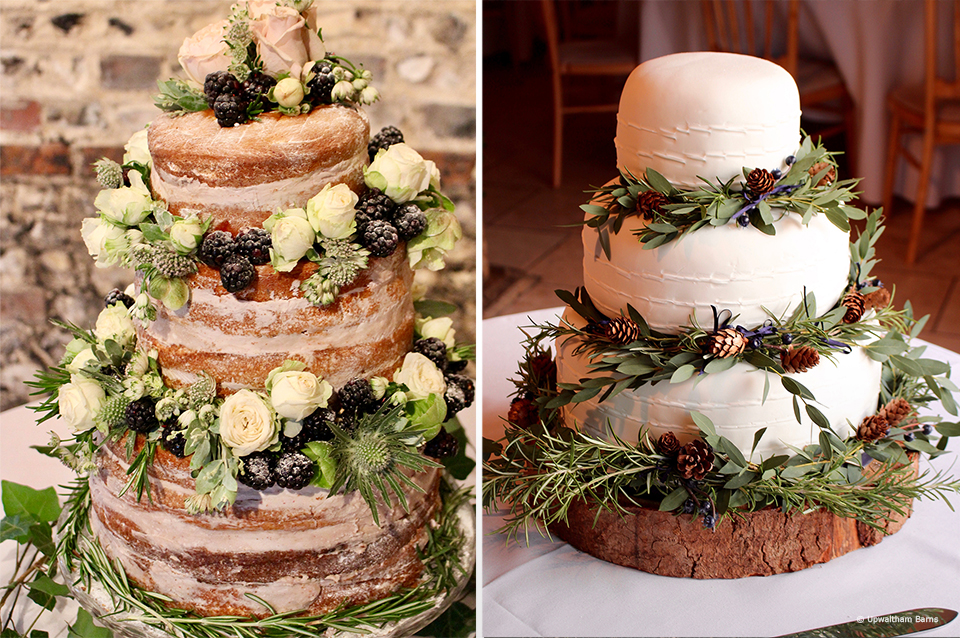 A white wedding cake is decorated with foliage and pine cones for a winter wedding at Upwaltham Barns