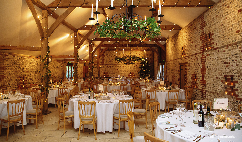The South Barn at Upwaltham Barns is set up for a Christmas inspired winter wedding reception