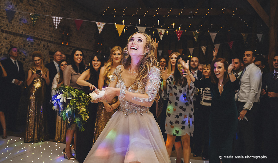 The bride tosses her wedding bouquet towards guests in the South Barn at Upwaltham Barns