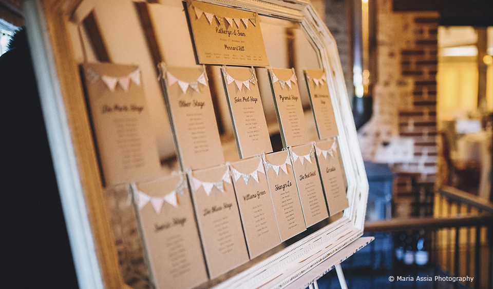 The couple added bunting to their table plan for their winter wedding at Upwaltham Barns
