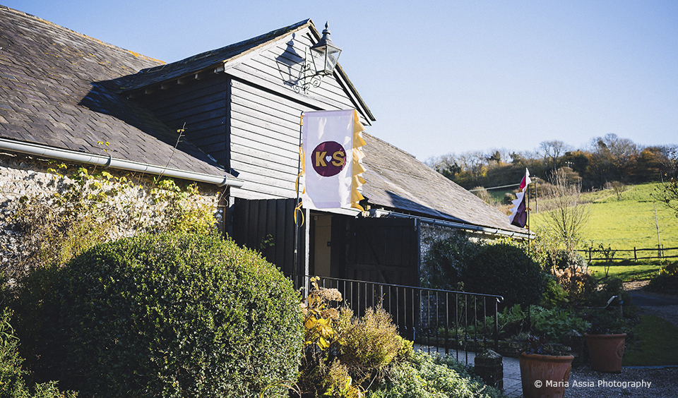 The couple added a paid of Glastonbury-themed flags outside Upwaltham Barns for their festival themed wedding
