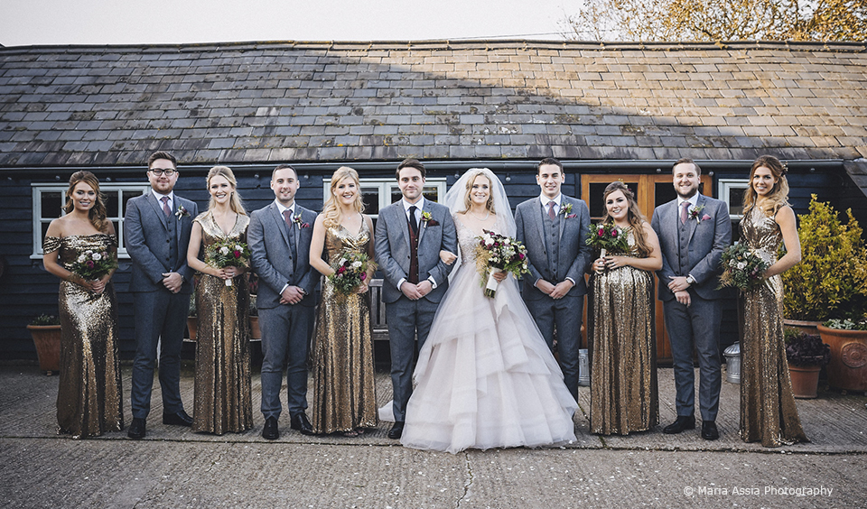 The wedding party gather for a photo after the wedding ceremony at Upwaltham Barns