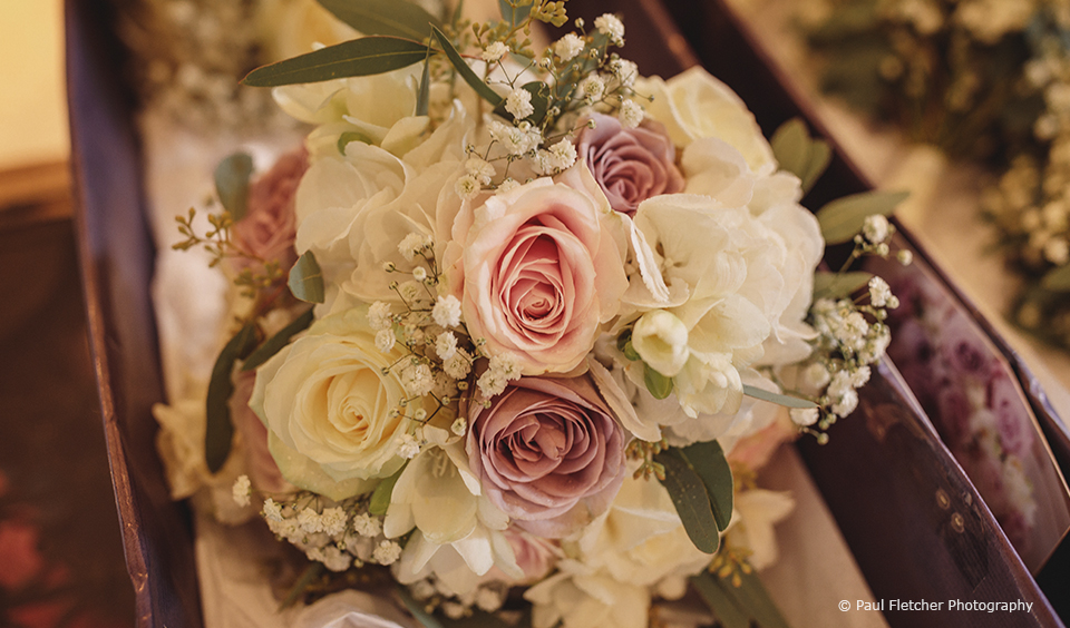The bridal bouquet for this rustic wedding at Upwaltham Barns was made up of pink and ivory roses