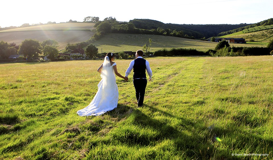 A bride and groom make the most of the countryside that surrounds Upwaltham Barns on their wedding day