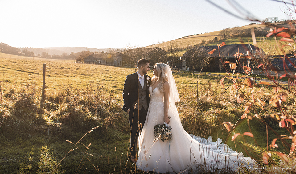 A bride and groom enjoy the countryside that surrounds Upwaltham Barns on their wedding day