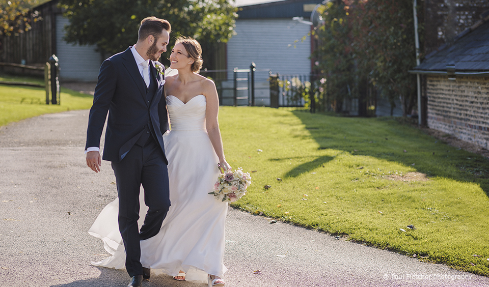 The bride and groom take a walk around Upwaltham Barns wedding venue in Sussex on their wedding day