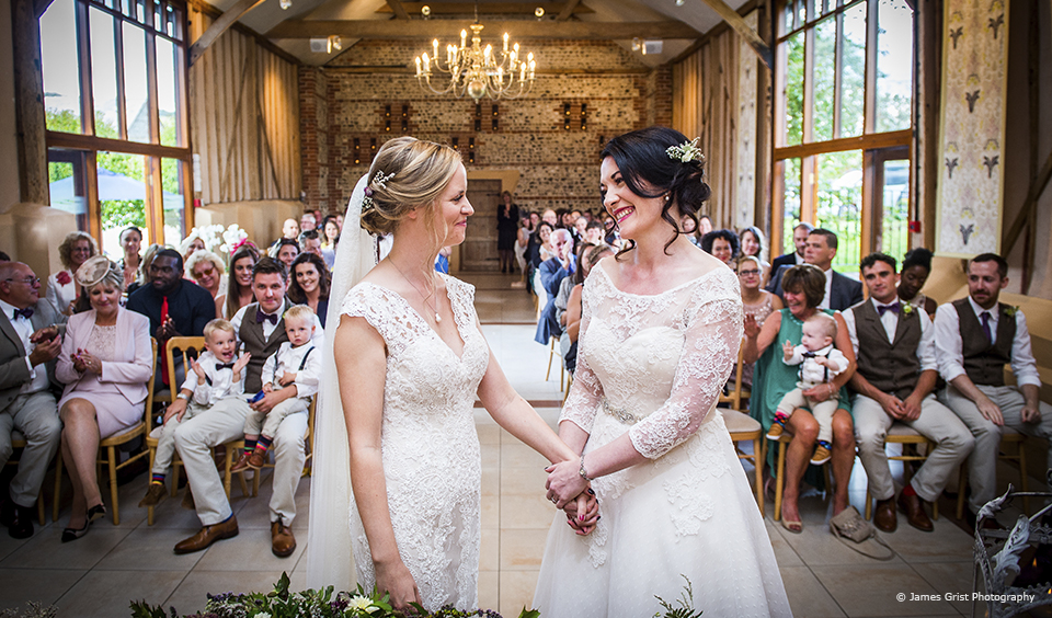 Brides say their vows during a wedding ceremony in the East Barn at Upwaltham Barns