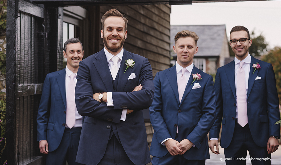 The groom and his groomsmen wore navy wedding suits and dusty pink ties for this rustic wedding at Upwaltham Barns