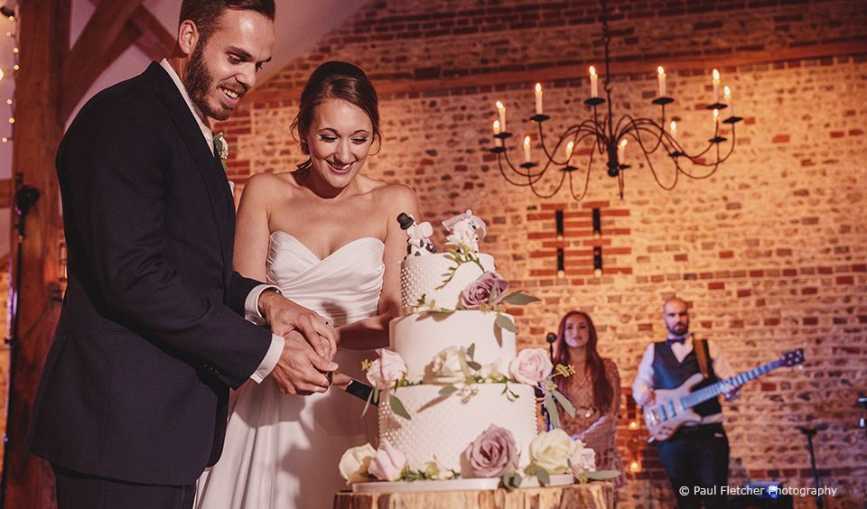 The newlyweds cut their wedding cake in front of guests during their evening wedding reception at Upwaltham Barns