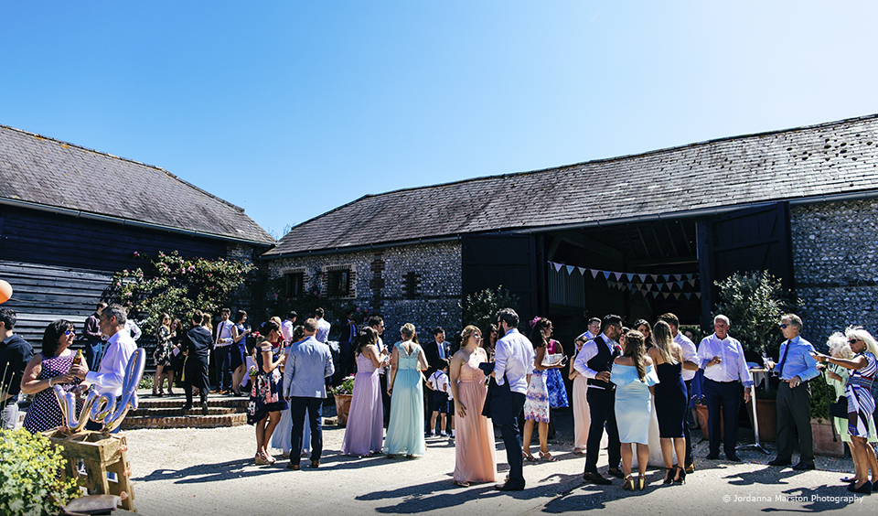Guests enjoy a wedding drinks reception in the courtyard at Upwaltham Barns
