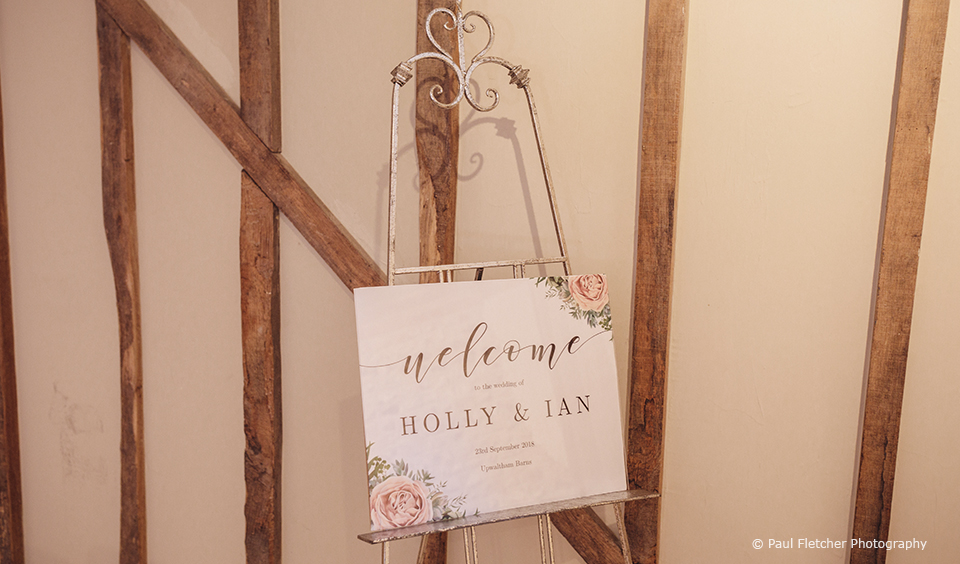 A sign welcomes guests to this rustic wedding at Upwaltham Barns in Sussex