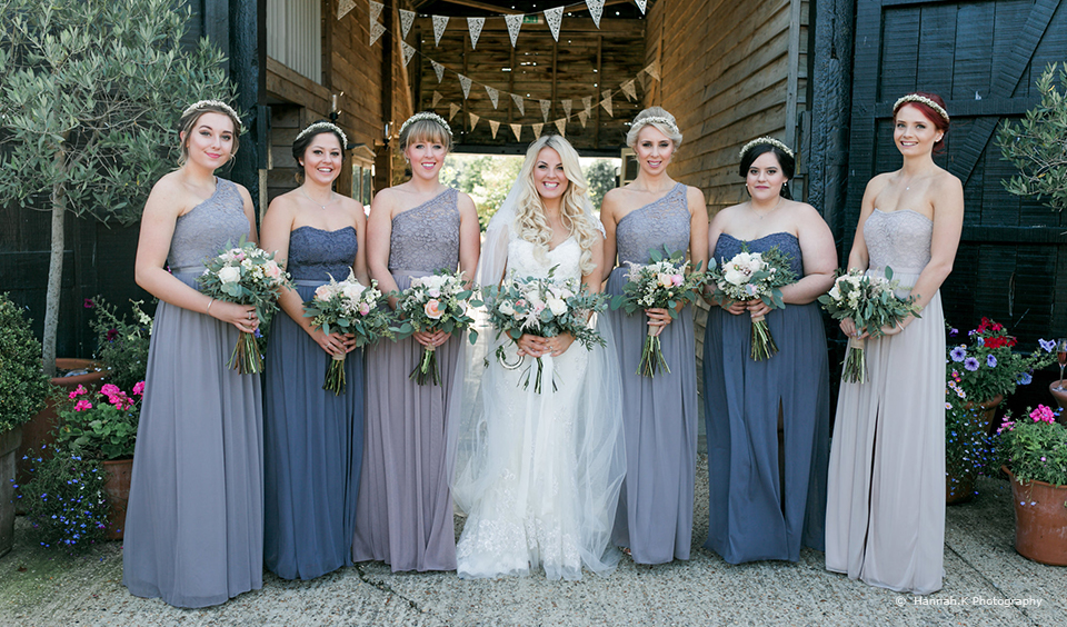 A bride and her bridesmaids stand with their wedding bouquets after the wedding ceremony at Upwaltham Barns