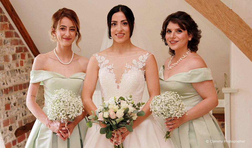 A bride stands with her bridesmaids who wear mint green bridesmaids dresses before the wedding ceremony at Upwaltham Barns