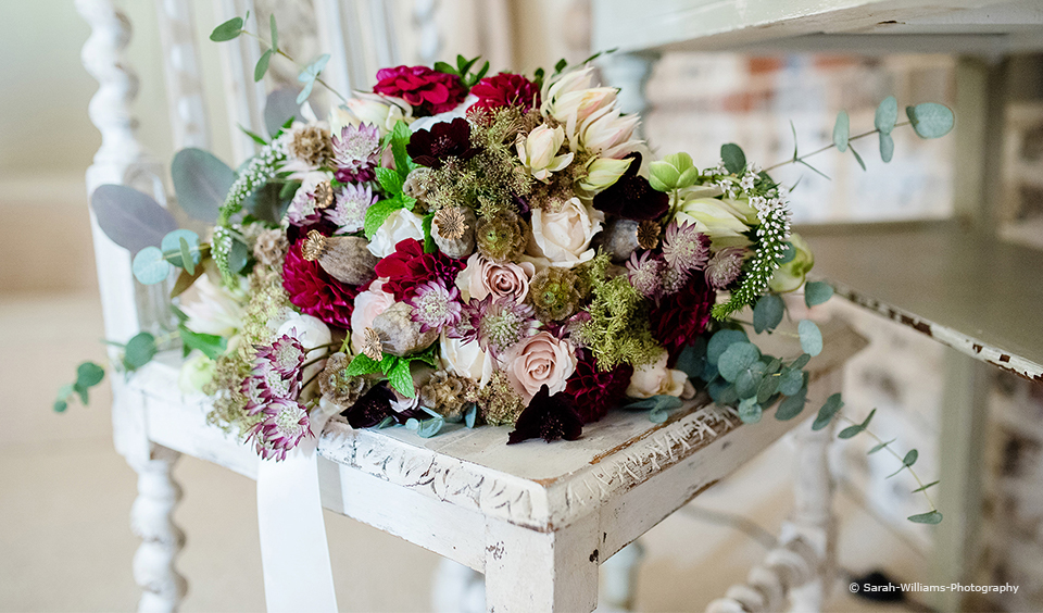 A wedding bouquet is made up of pink and burgundy florals for a wedding at Upwaltham Barns