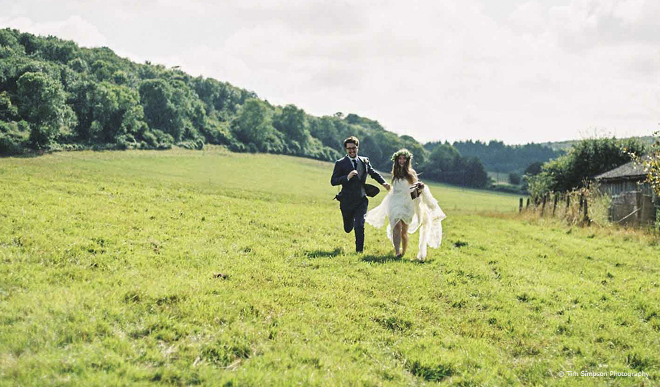 A boho bride and groom run through the countryside that surrounds Upwaltham Barns