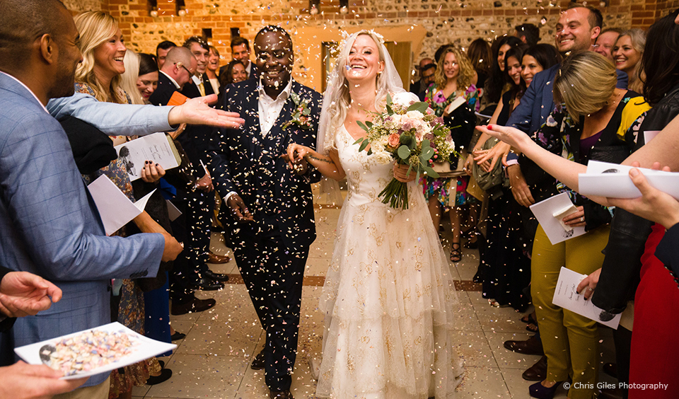 The bride and groom are showered in confetti following their wedding ceremony at Upwaltham Barns