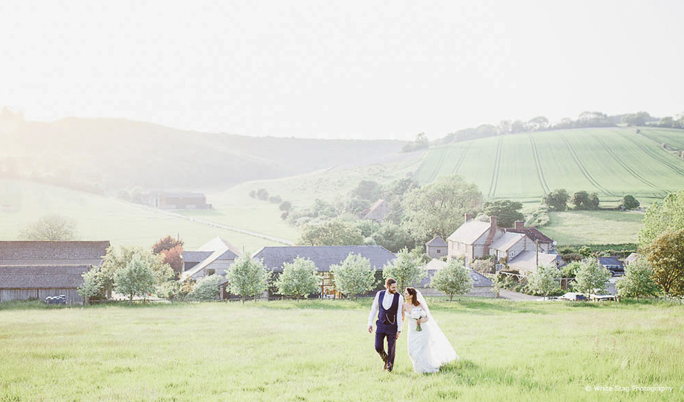 The bride and groom take a walk through the countryside on their wedding day at Upwaltham Barns