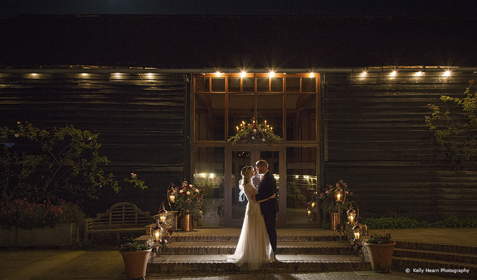 A bride and groom make the most of the courtyard at Upwaltham Barns for a romantic evening wedding photo
