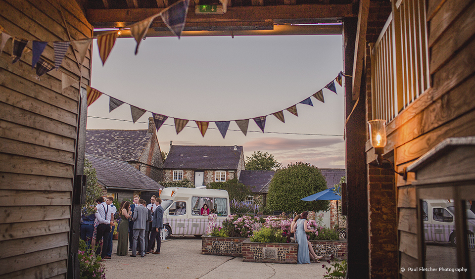 The courtyard and gardens at Upwaltham Barns are dressed for a rustic country wedding
