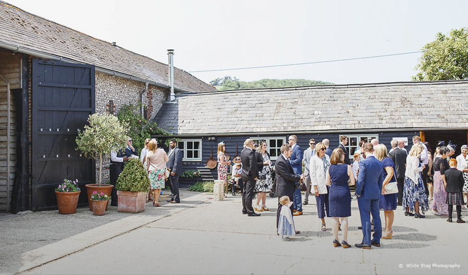 Guests enjoy the courtyard at Upwaltham Barns during a summer wedding reception