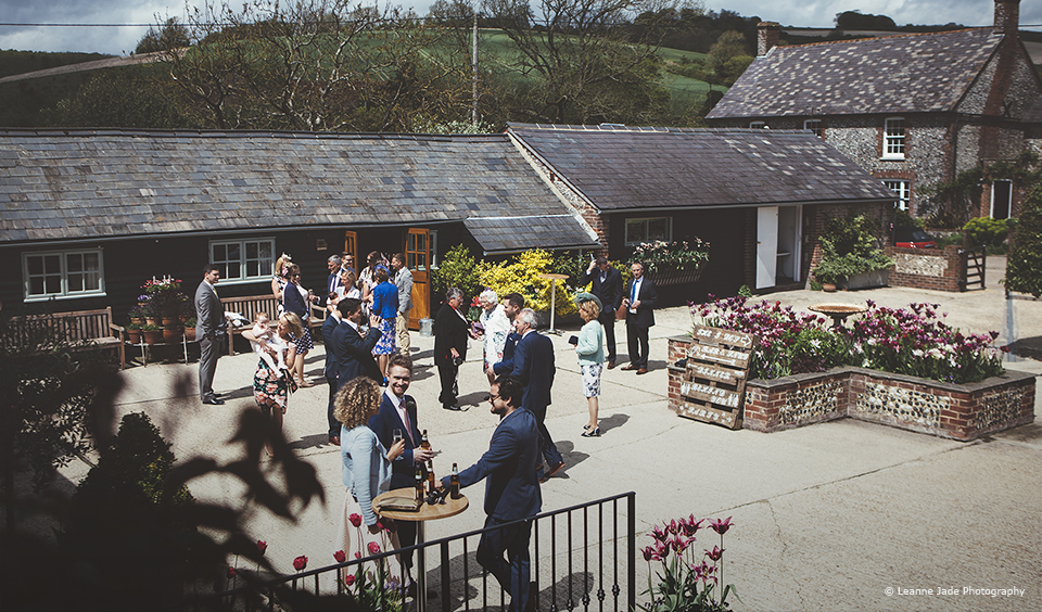 Wedding guests enjoy a drinks reception in the courtyard at Upwaltham Barns