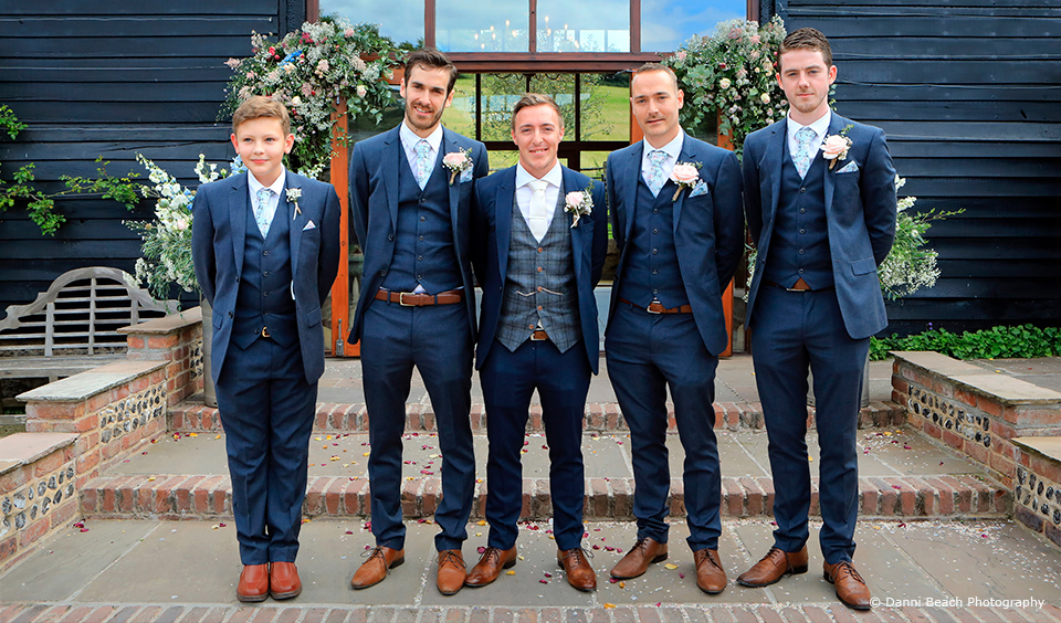 The groom and his groomsmen look smart in matching ties and pocket squares for a wedding at Upwaltham Barns