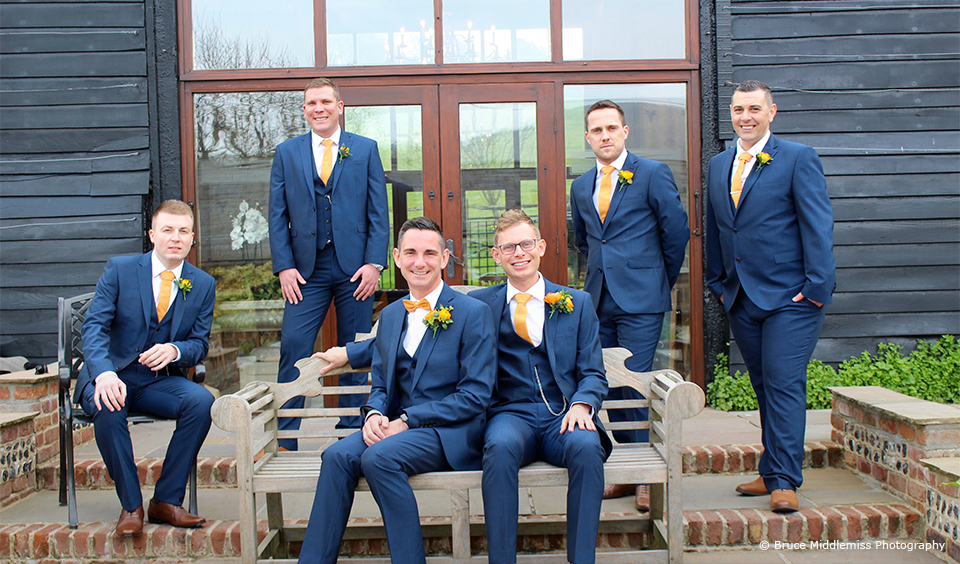 Grooms and groomsmen look smart in navy blue suits with bright yellow ties and buttonholes for a wedding at Upwaltham Barns