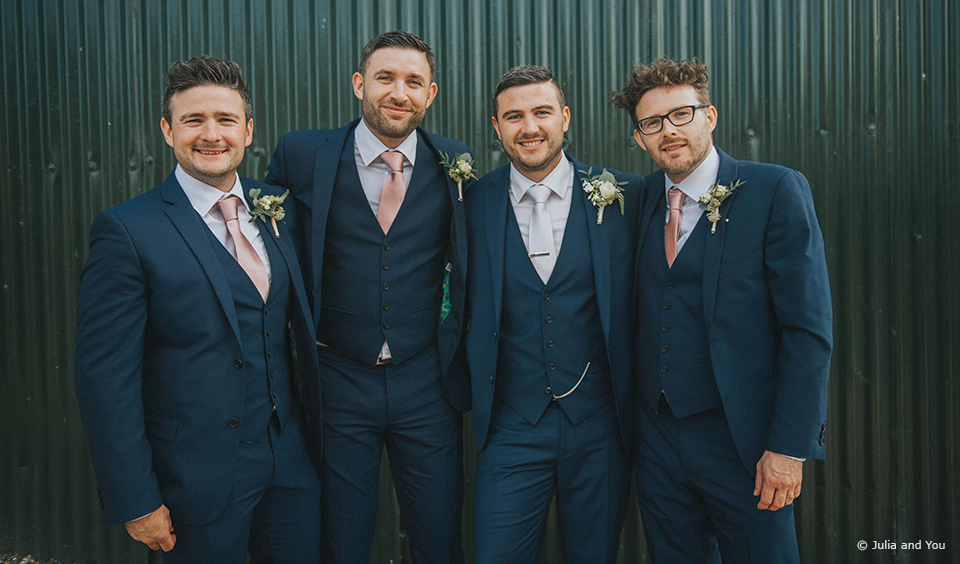 The groom and the groomsmen wear navy wedding suits for a spring wedding at Upwaltham Barns